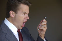Man yells at cell phone. Angry business man yells into cell phone Royalty Free Stock Photos
