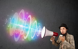 Man yells into a loudspeaker and colorful energy beam comes out Stock Image