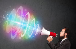 Man yells into a loudspeaker and colorful energy beam comes out Stock Photos