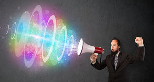 Man yells into a loudspeaker and colorful energy beam comes out Stock Images