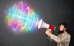 Man yells into a loudspeaker and colorful energy beam comes out Royalty Free Stock Image
