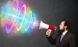 Man yells into a loudspeaker and colorful energy beam comes out Royalty Free Stock Photos