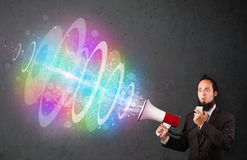 Man yells into a loudspeaker and colorful energy beam comes out Stock Photography