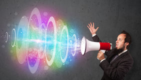 Man yells into a loudspeaker and colorful energy beam comes out Royalty Free Stock Photography