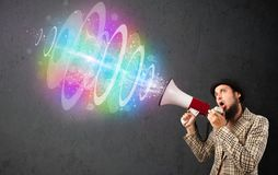 Man yells into a loudspeaker and colorful energy beam comes out Stock Photo