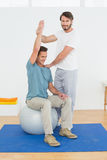 Man on yoga ball working with a physical therapist Royalty Free Stock Photo
