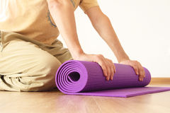 Man with yoga mat. Man hands holding yoga mat on floor Royalty Free Stock Photo