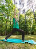 Man in a yoga pose outside. In a field surrounded by forest Stock Images