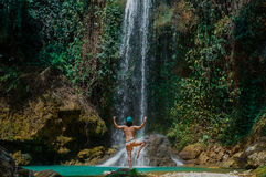 Man in yoga pose by waterfall
