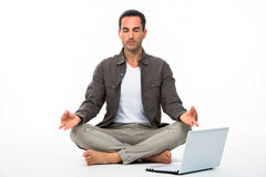 Man in yoga position with computer Royalty Free Stock Image