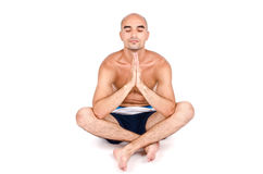 Man in yoga position. Topless man in shorts sitting relaxing and doing yoga. Royalty Free Stock Image