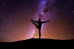 The man with yoga posture on the mountain at night. Man with yoga posture on the mountain on Milky Way background Stock Photos