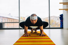 Man Yoga Practice Pose indoors, city panoramic view at background Royalty Free Stock Photography