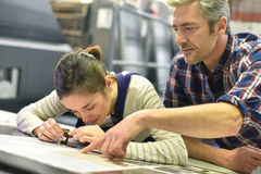 Man and young apprentice checking on print quality Royalty Free Stock Images