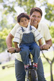 Man and young boy on a bike outdoors smiling Stock Photo