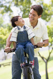 Man and young boy on a bike outdoors smiling. At each other stock photography