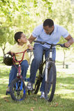 Man and young boy on bikes outdoors smiling. At one another royalty free stock photos