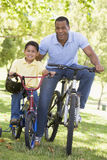 Man and young boy on bikes outdoors smiling Royalty Free Stock Photo