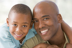 Man and young boy embracing and smiling Stock Photos