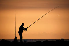 Silhouette of  a Father and son fishing at sunset. Father and son fishing in ocean surf at sunset Royalty Free Stock Photo