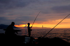 Father and son fishing at sunset silhouette. Father and son fishing in ocean surf at sunset Stock Images