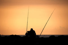 Silhouette of a father and son fishing at sunset. Father and son fishing in ocean surf at sunset Royalty Free Stock Images