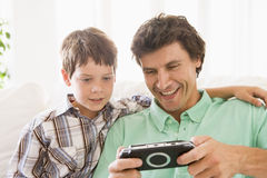 Man and young boy with handheld game Royalty Free Stock Photography