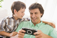 Man and young boy with handheld game. Smiling Stock Images
