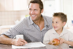Man and young boy in kitchen with newspaper apple. Smiling man and young boy in kitchen with newspaper apple Stock Images