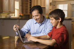 Man and Young Boy on Laptop stock photo