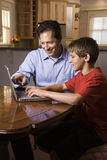 Man and Young Boy on Laptop Stock Images