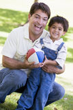 Man and young boy outdoors with football smiling. At camera stock photos
