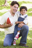 Man and young boy outdoors with football smiling Royalty Free Stock Photo