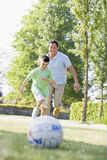 Man and young boy outdoors playing soccer. And having fun Stock Images
