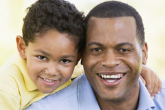 Man and young boy outdoors smiling. At camera royalty free stock photo