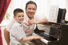 Man and young boy playing piano and smiling Royalty Free Stock Photo