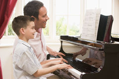 Man and young boy playing piano and smiling Royalty Free Stock Photos