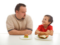 Man and young boy rival over food royalty free stock photography