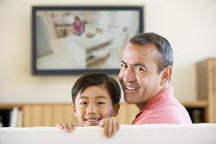 Man and young boy in room with flat screen Stock Images
