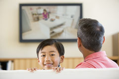 Man and young boy in room with flat screen Stock Photography