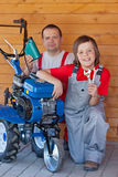 Man and young boy servicing a small tiller machine. Man and young boy servicing tiller machine - preparing for spring operations stock photo