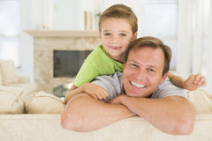 Man and young boy sitting in living room smiling. Close up of man and young boy sitting in living room smiling Stock Photo