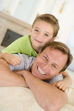 Man and young boy sitting in living room smiling stock image