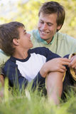 Man and young boy sitting outdoors smiling Royalty Free Stock Image