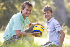 Man and young boy with soccer ball smiling royalty free stock photo