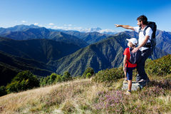 Man and young boy standing in a mountain meadow Stock Photos