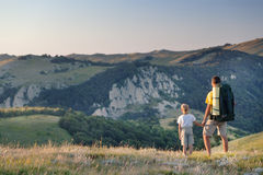 Man and young boy standing in a mountain meadow. Stock Photos