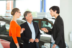 Man with young couple in car dealership Stock Image