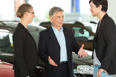 Man with young couple in car dealership Stock Photos