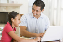 Man and young girl with laptop. In dining room smiling stock photos